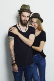 Beautiful couple in hat and posing over white background together. Hipster boy and girl Stock Photo