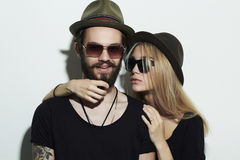Beautiful couple in hat wearing trendy glasses together. Hipster boy and girl Stock Photos