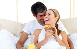 Beautiful couple having breakfast lying in the bed Royalty Free Stock Photo