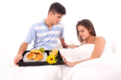 Beautiful couple having breakfast lying in the bed royalty free stock image
