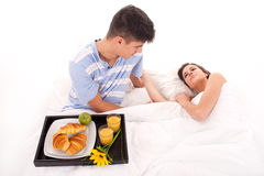 Beautiful couple having breakfast lying in the bed stock photos