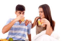Beautiful couple having breakfast lying in the bed. Portrait of a beautiful young couple with breakfast in bed stock photography