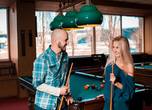 Beautiful couple having fun and playing billiards Royalty Free Stock Photo