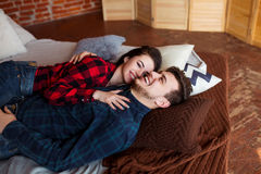 Beautiful couple having fun, smiling and hugging at home. Young man and woman enjoy spending time together. Stock Photo