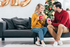 Beautiful couple holding cups of tea and looking at each other at home. With christmas tree stock images