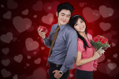 Beautiful couple holding a gift and flower Stock Photography