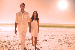 Beautiful couple holding hands and walking towards camera. At the beach Stock Photography