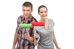 Beautiful couple holding painting rollers. Royalty Free Stock Photo
