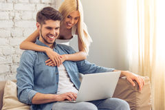 Beautiful couple at home with gadget Stock Photography