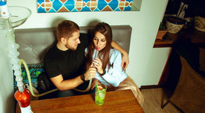 Beautiful couple at the hookah bar smokes shisha Royalty Free Stock Photo