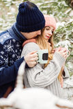 Beautiful couple with hot tea in cups in forest Stock Image
