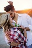 Beautiful couple hugging and dating on beach. At sunset Stock Photos
