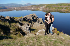 Beautiful couple hugging and laughing outdoor. Beautiful couple hugging and laughing on a lake background Royalty Free Stock Image