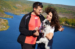 Beautiful couple hugging and laughing outdoor. Beautiful couple hugging their dog and laughing on a lake background Royalty Free Stock Images