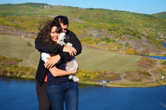 Beautiful couple hugging and laughing outdoor. Beautiful couple hugging their dog and laughing on a lake background Stock Photos