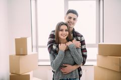 Beautiful young couple is hugging, looking at camera and smiling while standing near the boxes ready to move royalty free stock image