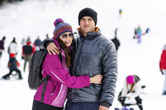Beautiful couple hugging and smiling outdoor on a ski slope Stock Photos