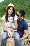 Beautiful couple hugging their white dog outdoor. Beautiful young couple having fun with their dog in the mountain Stock Photo