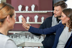 Beautiful couple at the jewelry store. A ring symbolizing eternity. Beautiful happy couple trying on rings with the assistance of a jewelry store clerk stock images