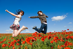 Beautiful couple jumping in the poppy field Stock Photography