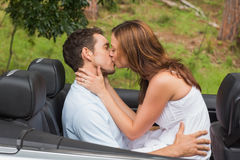 Beautiful couple kissing in back seat. Of a convertible Royalty Free Stock Image
