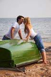 Beautiful couple kissing on a beach. Near old boat Stock Photo