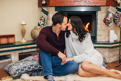 Beautiful couple kissing by the fireplace. Beautiful couple in love near fireplace, posing for the camera Stock Photos