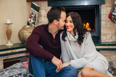 Beautiful couple kissing by the fireplace. Beautiful couple in love near fireplace, posing for the camera Stock Images