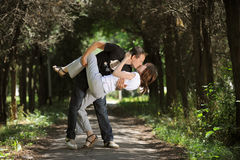 Beautiful couple kissing on a park. Kissing young couple in the middle of an alley Royalty Free Stock Photos