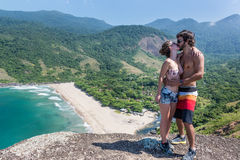 Beautiful couple kissing at a stone cliff, Brazil. Kissing at the edge of a perfect beach at Rio do Janeiro Brazil. South America Stock Images