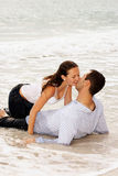 Beautiful couple kissing in the tide. Beautiful young couple  at the beach, about to kiss as the tide comes up and covers them with water, getting washed away Stock Photo