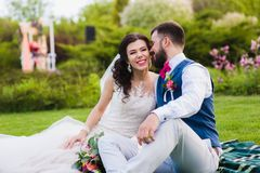 Beautiful couple laughing and joking together. Groom telling something funny to the bride while they and sitting in the green park. Beautiful couple laughing and Royalty Free Stock Photo