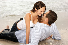 Beautiful couple laying on beach smiling at each o. Beautiful couple laying on the beach looking into each others eyes, smiling and happy Stock Image