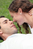 Beautiful couple laying in grass looking into each. Beautiful loving couple laying in grass with faces close together looking into each others eyes about to kiss Stock Images