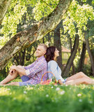 Beautiful couple leaning on each other backs. And having a picnic in the garden Stock Images