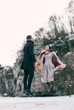 Beautiful couple levitates above the frozen lake. Guy and a girl are jumping of happiness among high rocks Stock Photography