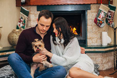 Beautiful couple with little dog in love near fireplace Stock Photo