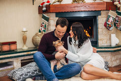 Beautiful couple with little dog in love near fireplace Stock Photos