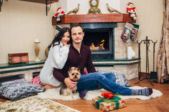 Beautiful couple with little dog in love near fireplace Royalty Free Stock Photos
