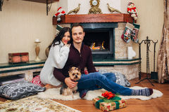 Beautiful couple with little dog in love near fireplace Royalty Free Stock Photography