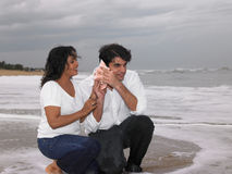 A beautiful couple looking at a conch Stock Photography