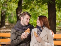 A beautiful couple are looking at each other and holding a croissant. A beautiful couple in love looks at each other cute and smiles and holds a croissant. In Royalty Free Stock Image