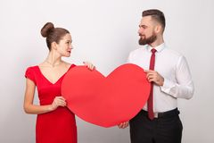 Beautiful couple looking each other, holding red heart, their lo. Ve. Indoor, studio shot, on gray background stock images