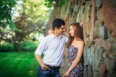 Beautiful couple looking at each other. Near a stone wall Royalty Free Stock Photos