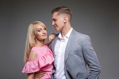 Beautiful couple is looking at each other and smiling while standing straight on gray background. stock image