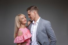 Beautiful couple is looking at each other and smiling while standing straight on gray background. royalty free stock image