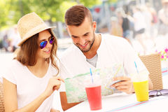 Beautiful couple looking at map in a cafe Stock Photo