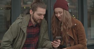 Beautiful couple looking at smartphone while sitting in outdoors restaurant. Beautiful couple using phone while sitting in outdoors restaurant stock video footage