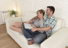 Beautiful couple in love on couch together with laptop computer happy at home using internet Stock Photography