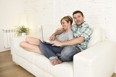 Beautiful couple in love on couch together with laptop computer happy at home using internet Stock Images